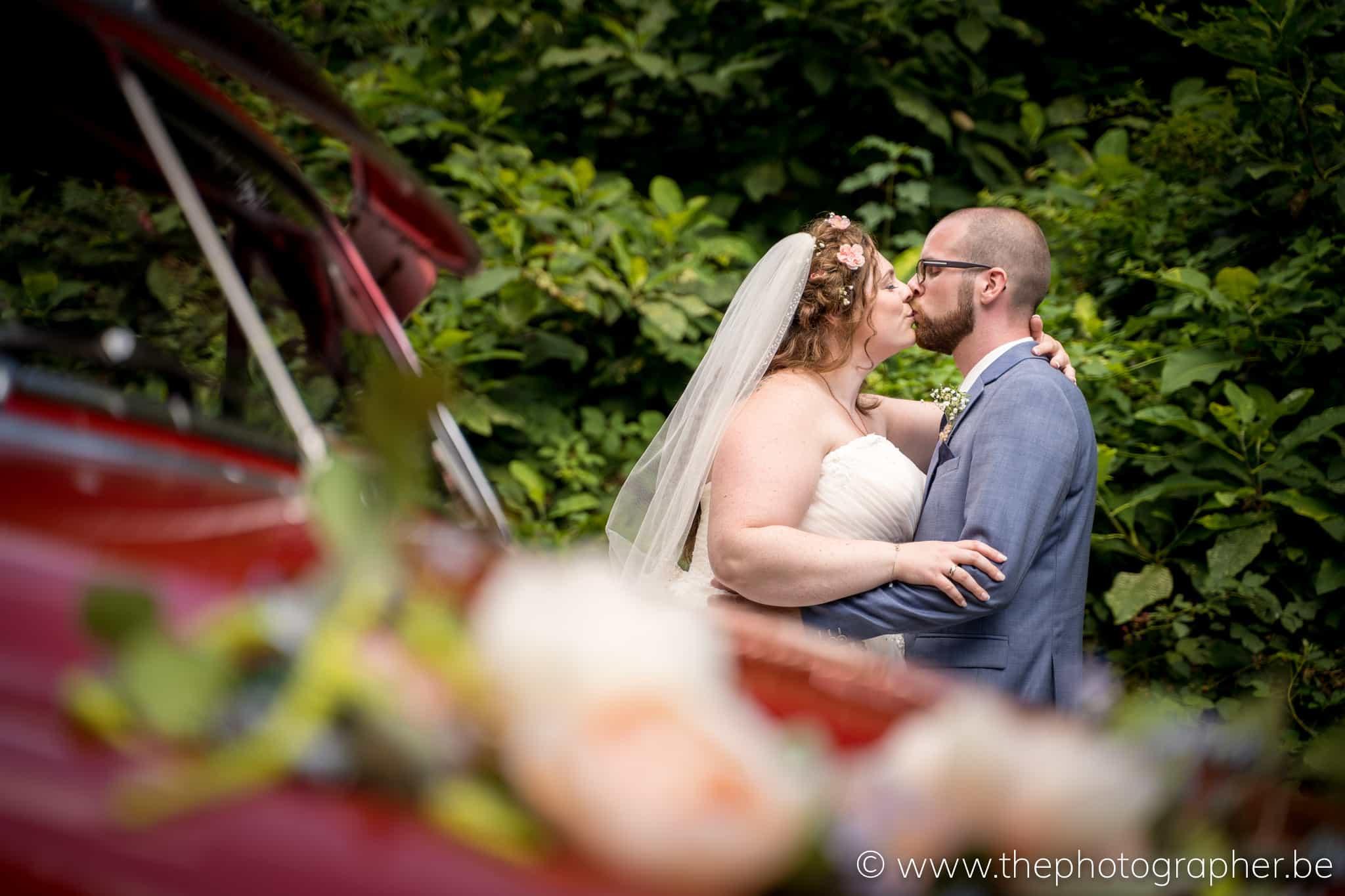 Huwelijksfoto met oldtimer en boeket